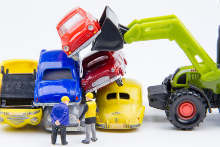 Het miniatuur uiterst kleine speelgoed die zaken doen over begraafplaatsauto werd beschadigd door een autoongeval en oude auto's. Detail van industriële kraanklauw die oude auto voor recycling in autoschrootwerf grijpen. Auto industrie achtergrond