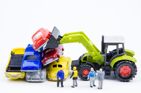 doing business: Miniature tiny toys doing business about cemetery car was damaged by a car accident and old cars.Detail of industrial crane claw grabbing old car for recycling in car scrap yard. Car industry background