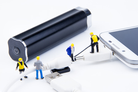 Miniature tiny toys team of engineers are doing connected cable backup battery power bank to the smartphone for charging.Theme communication technology background