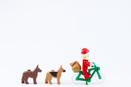 mini bike: Nonthaburi, Thailand - November, 26, 2016 : Lego dog follow Lego Santa Claus ride a bicycle giving gifts at Christmas.Theme Christmas day background.