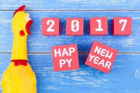 Toy yellow shrilling chicken and Happy new year 2017 number on red paper box cubes on blue wooden background with copy space.Year of the Cock.2017 New Year concept background.