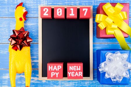 yellow paper: Toy yellow chicken, Present gift box, Blackboard and Happy new year 2017 number on red paper box cubes on blue wooden background with copy space.Year of the Cock.2017 New Year concept background.