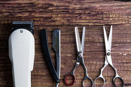 Stylish Professional Barber Clippers, Hair Clippers,  Hair scissors, razor, Haircut accessories on wood background with copy space Stock Photo