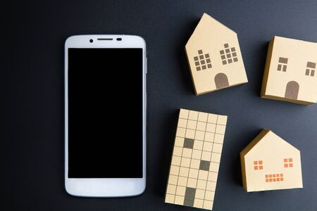architectural model: Home architectural model paper box cubes and smart phone on black background with copy space.Real estate concept. Stock Photo