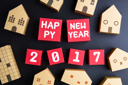 architectural model: Happy new year 2017 number on red paper box cubes and home architectural model paper box cubes on black background with copy space.Christmas and New Year background
