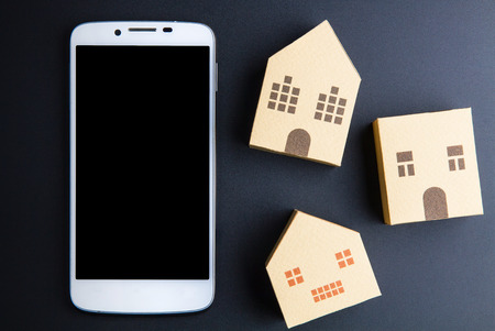 architectural model: Home architectural model paper box cubes and smart phone on black background with copy space.Real estate concept