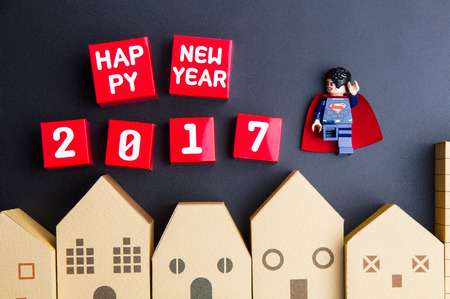 architectural model: Nonthaburi, Thailand - December, 15, 2016 : Lego Super Man are flying in the sky and Happy new year 2017 number red paper box cubes over home architectural model on black background.