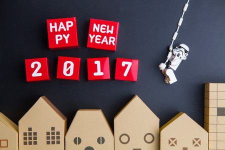 architectural model: Nonthaburi, Thailand - December, 15, 2016 : Lego star wars stormtrooper are rope hung swinging to Happy new year 2017 number red paper box cubes over home architectural model on black background.