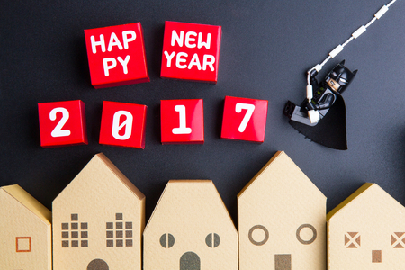 Nonthaburi, Thailand - December, 15, 2016: Lego Bat Man zijn touw hing swingend naar Gelukkig Nieuwjaar 2017 nummer rood papier vak kubussen over huis architectonisch model op zwarte achtergrond.