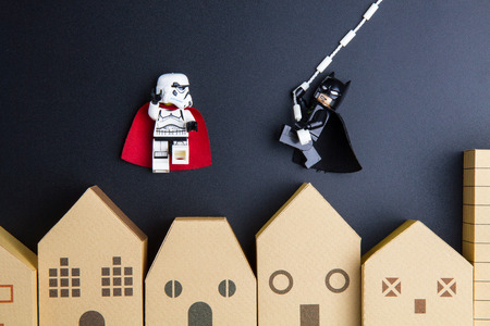 architectural model: Nonthaburi, Thailand - December, 15, 2016 : Lego star wars stormtrooper are flying in the sky and Lego Bat Man are rope hung swinging over home architectural model on black background.