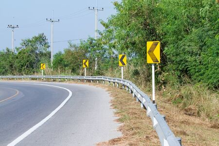Yellow road signs warn Drivers for Ahead Dangerous Curve.