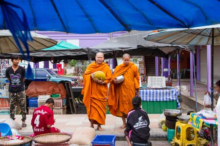 Uthai Thani, Thailand - December, 17, 2016 : Unidentified monks receive food offering from people in the morning market.Offering food is one of most common rituals in Buddhism.