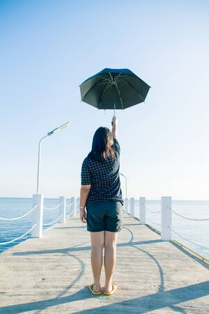Teenage woman standing holding an black umbrella on white cement bridge fishing pier extending into the sea at Khlong Ta Kok Bang Pu Samut Prakan, Thailand. Stock Photo
