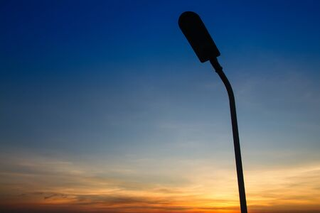Silhouette of streetlight with beautiful sunset twilight sky at the sea Stock Photo