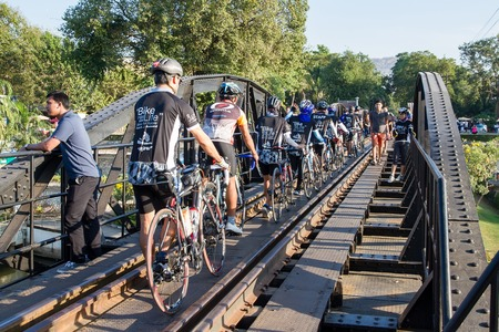 Kanchanaburi, Thailand - December, 25, 2016 : Unidentified Cyclists Tourist walk on The Railway Bridge on the River Kwai at Kanchanaburi,Thailand.This bridge is famous for its history in second world war.