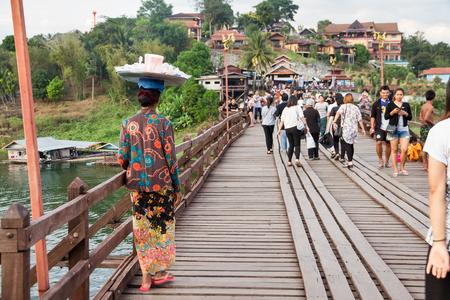 december 25: Kanchanaburi, Thailand - December, 25, 2016 : Unidentified Tourist walk on the wooden bridge (Mon Bridge) over the river in sunset at Sangkhlaburi, Mon Bridge is the longest bridge in Thailand