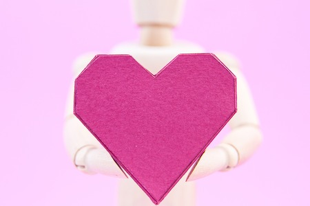 Wooden dummy holding paper box red heart shape on pink background with copy space for your text.Concept Valentine's Day, Day of love