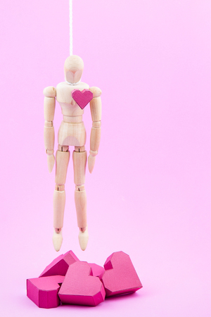hanged: Wooden dummy hanged himself on a pile of paper box red heart shape on pink background with copy space for your text.Concept Valentines Day, Day of love.