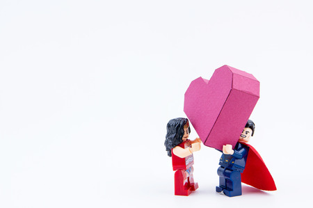 Nonthaburi, Thailand - January, 09, 2017 : Lego super man showing love give a paper box red heart shape to lego super woman on white background.Concept Valentines Day Editorial