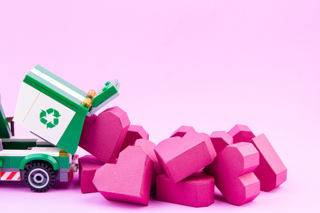 Nonthaburi, Thailand - January, 10, 2017 : Lego star wars stormtrooper carry a paper box red heart shape from waste trucks to recycling is a new heart on pink background .Concept Valentines Day. Editorial