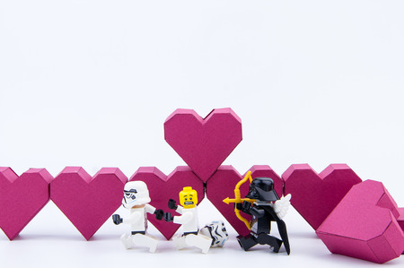 stormtrooper: Nonthaburi, Thailand - January, 09, 2017 : Lego stormtrooper running away lego cupid darth vader love chase distribution.Stand on the paper box red heart shape on white background.Concept Valentines Day