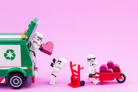 stormtrooper: Nonthaburi, Thailand - January, 10, 2017 : Lego star wars stormtrooper carry a paper box red heart shape from waste trucks to recycling is a new heart on pink background .Concept Valentines Day. Editorial