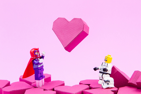 Nonthaburi, Thailand - January, 11, 2017 : Lego X-man Magneto take lifting the float up paper box red heart shape off the ground with super powers on pink background.Concept Valentines Day