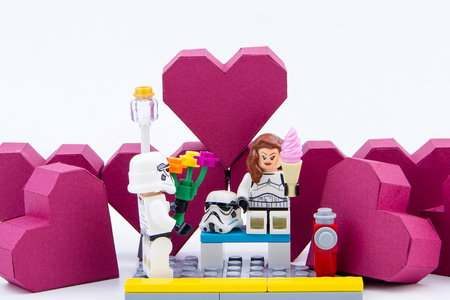 stormtrooper: Nonthaburi, Thailand - January, 09, 2017 : Lego stormtrooper showing love give a flower to lego stormtrooper woman.Stand on the paper box red heart shape on white background.Concept Valentines Day Editorial