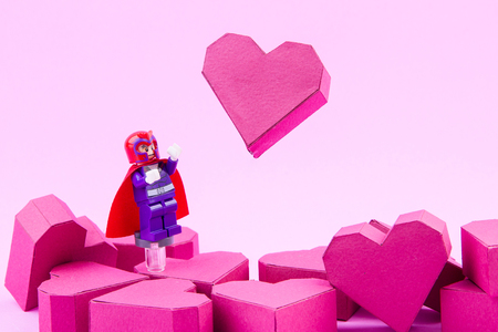 magneto: Nonthaburi, Thailand - January, 11, 2017 : Lego X-man Magneto take lifting the float up paper box red heart shape off the ground with super powers on pink background.Concept Valentines Day