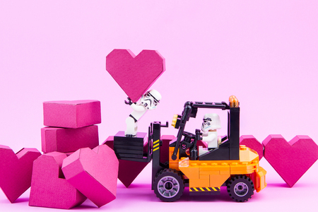 Nonthaburi, Thailand - January, 09, 2017 : Lego star wars stormtrooper drive forklift carry a paper box red heart shape on pink background with copy space for your text.Concept Valentines Day. Editorial