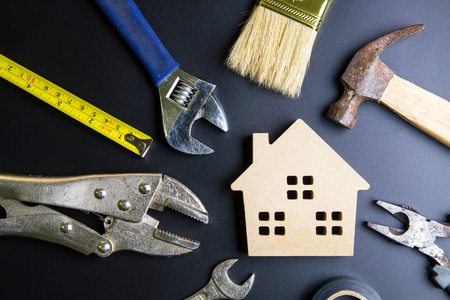 Wooden house toy and construction tools on black background with copy space.Real estate concept, New house concept, Finance loan business concept, Repair maintenance concept 스톡 콘텐츠