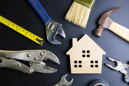 Herramientas de juguete y construcción de casa de madera sobre fondo negro con espacio de copia. Concepto de bienes raíces, concepto de casa nueva, concepto de negocio de préstamo de finanzas, concepto de mantenimiento de reparación