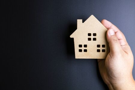 Mans hand holding wooden house toy on black background with copy space.Real estate concept, New house concept, Finance loan business concept