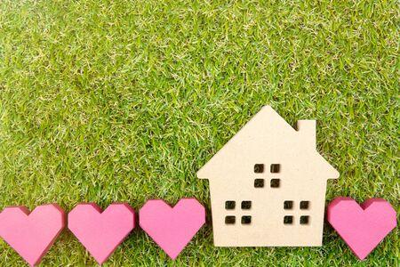 Hölzernes Hausspielzeug und rote Herzform des Papierkastens auf grünem Gras des Bodens mit Kopienraum Wirklichkeitskonzept, neues Hauskonzept, Liebeshauskonzept, Finanzkreditgeschäftskonzept Standard-Bild