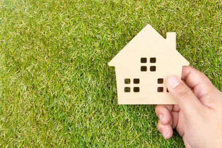 La mano del hombre que sostiene el juguete de madera de la casa en la hierba verde de tierra con el espacio de la copia. Concepto inmobiliario, concepto de la casa nueva, concepto de la casa del amor, concepto del negocio del préstamo de las finanzas
