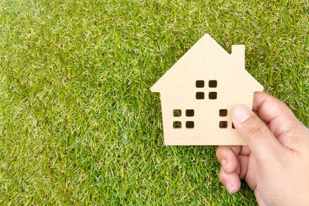 Mans hand holding wooden house toy on ground green grass with copy space.Real estate concept, New house concept, Love house concept, Finance loan business concept Stock Photo