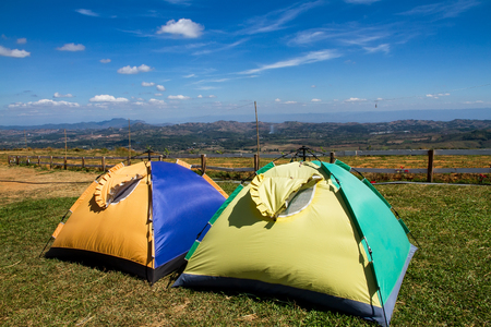 campsite: Tent on a grass under white clouds and blue sky Stock Photo