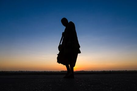 Silhouette of monk feet walking on concrete ground for people offering food in twilight morning near Mekong river bank