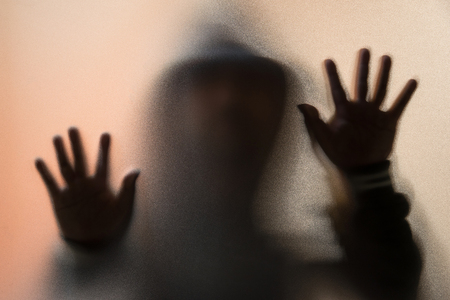 Shadow blur of horror man in jacket with hood.Hands on the glass.Dangerous man behind the frosted glass.Mystery man.Halloween background.Blur picture