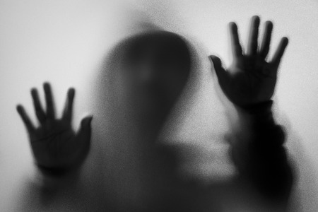 Shadow blur of horror man in jacket with hood.Hands on the glass.Dangerous man behind the frosted glass.Mystery man.Halloween background.Black and white picture.Blur picture