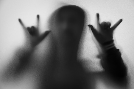 Shadow blur of horror man in jacket with hood.Hands do as a symbol love on the glass.Dangerous man behind the frosted glass.Mystery man.Halloween background.Black and white picture.Blur picture Stock Photo