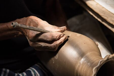 Nonthaburi, Thailand - February, 22, 2017 : Hand of potter man traditional pottery making detailed a jar before took in the kiln at Koh Kret Nonthaburi, Thailand. Editorial