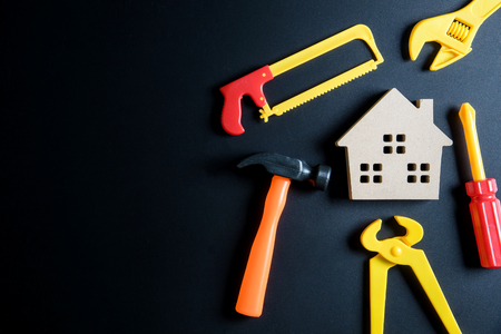 Wooden house toy and construction tools toy on black background with copy space.Home Repair concept, Repair maintenance concept, Renovation concept. Stock Photo