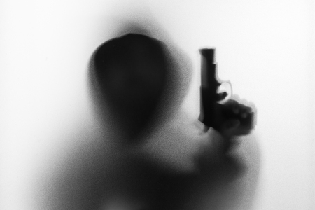 Shadow blur of horror man in jacket with hood gun in his hand.Dangerous man behind the frosted glass.Mystery man.Halloween background.Black and white picture.Blur picture