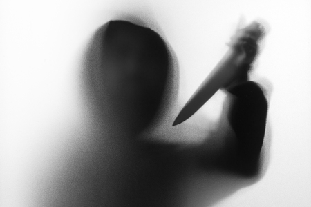 Shadow blur of horror man in jacket with hood knife in his hand.Dangerous man behind the frosted glass.Mystery man.Halloween background.Black and white picture.Blur picture Stock Photo
