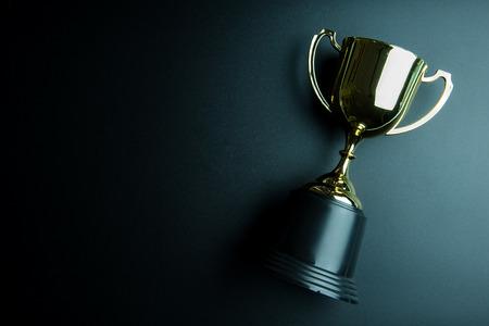 Gouden die trofee op zwarte achtergrond met exemplaarruimte wordt geïsoleerd Conceptenwinnaar