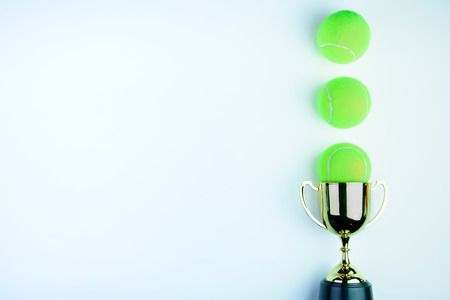 Golden trophy and Tennis ball isolated on white background with copy space.Concept winner of the sport