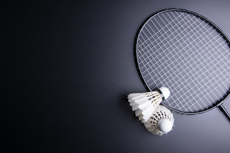 Two shuttlecocks and badminton racket on black background.Sport concept, Copy space image for your text Фото со стока