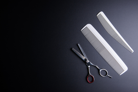 Stylish Professional Barber Scissors and white comb on black background. Hairdresser salon concept, Hairdressing Set. Haircut accessories. Copy space image, flat lay Фото со стока