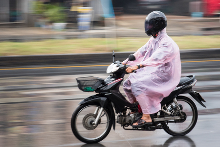 Nonthaburi, Thailand - April, 04, 2017 : Motion Blurred panning photo of Unidentified name man riding motorcycle in the rain on road at Nonthaburi, Thailand.